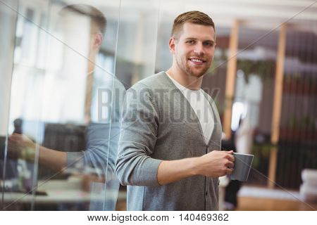 Portrait of businessman holding coffee cup in office