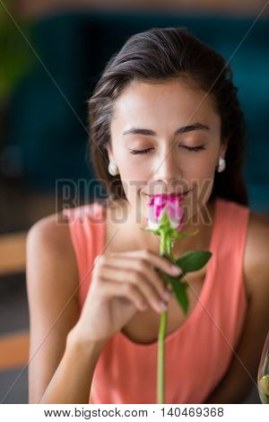 Portrait of smiling woman smelling a rose in restaurant
