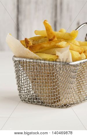 French fries in metal wire basket over white kitchen table. Selective focus