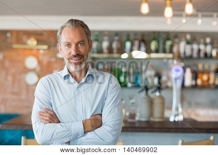 Portrait of smiling man standing with arms crossed in restaurant
