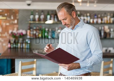 Confident man writing in a file in restaurant