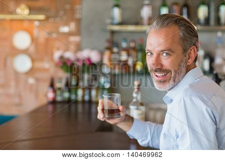 Portrait of man sitting at bar counter holding glass of whiskey in restaurant