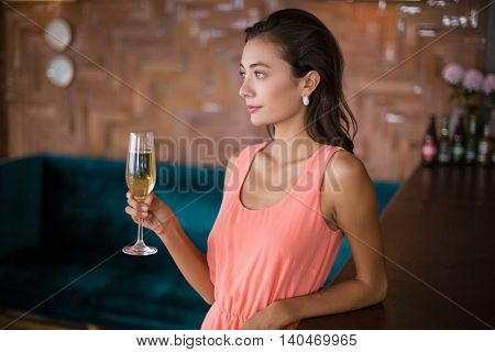 Beautiful woman holding a champagne flute in restaurant