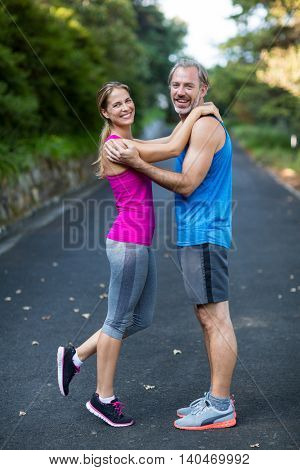 Smiling athletic couple embracing each other on the road
