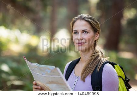 Confident woman standing with map in forest