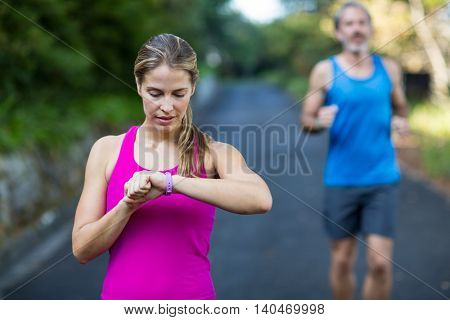 Fit woman checking time on wristwatch after jogging