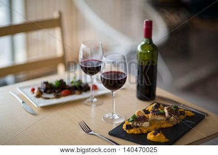 Plate of meal with glass of red wine in restaurant