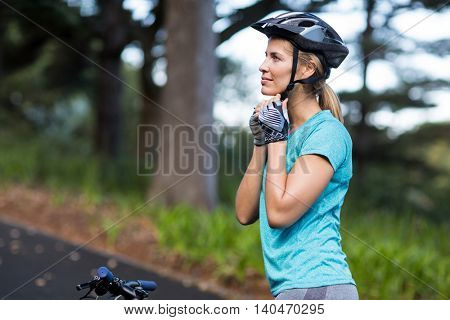 Female athletic wearing bicycle helmet on road