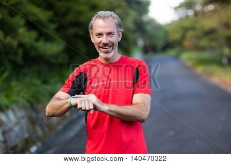 Athletic man checking time on wristwatch after jogging