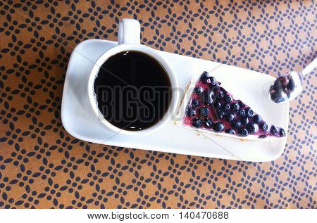 Cup of coffee with blueberry cake on the plate at the table