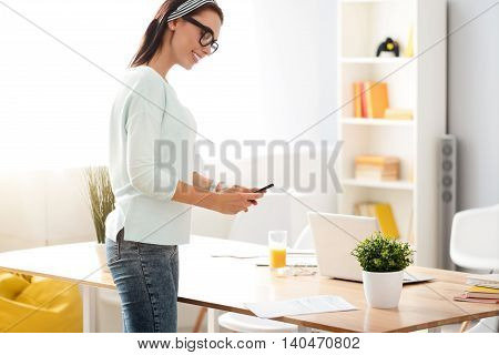 Diligent worker. Cheerful smiling charming woman standing near table and expressing joy while using cell phone