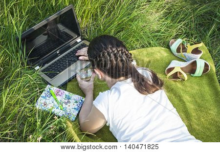 girl lying on the grass with a laptop and a notebook