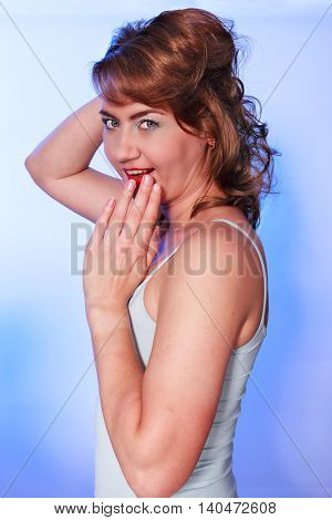 Waist portrait of a young attractive woman. Studio shot with blue background