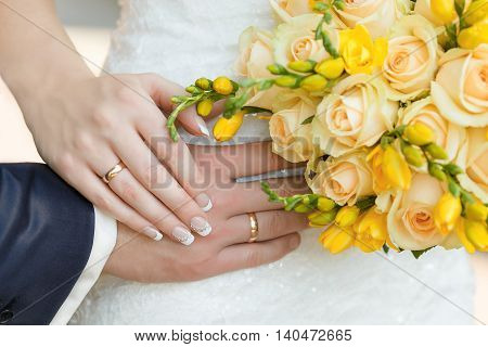 male and female hand with rings and Bridal bouquet of yellow roses