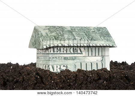 House origami made from hundred dollar bills standing on black soil isolated on white background