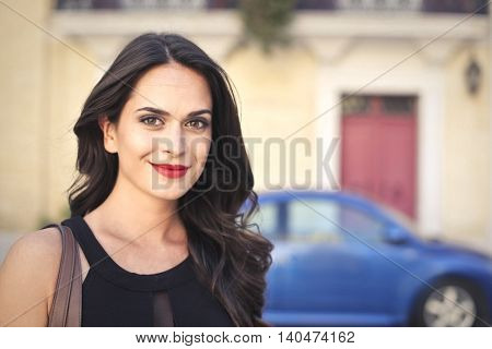 Smiling dark-haired woman wearing red lipstick