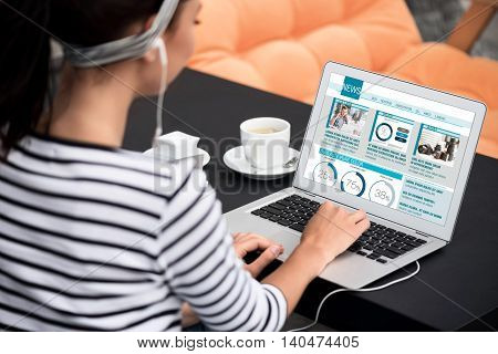 In whirlwind of information. Pleasant young woman sitting at the table and listening to music while surfing the Internet