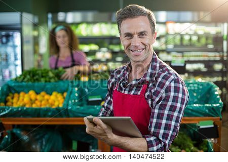 Portrait of smiling staff using digital tablet in organic section of supermarket