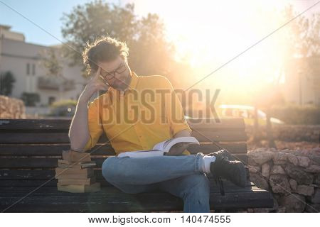 Man reading books sitting on a bench