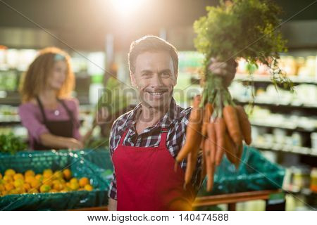 Portrait of smiling male staff holding bunch of carrots in organic section of supermarket