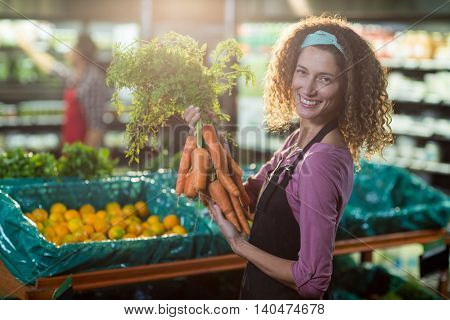 Portrait of smiling female staff holding bunch of carrots in organic section of supermarket