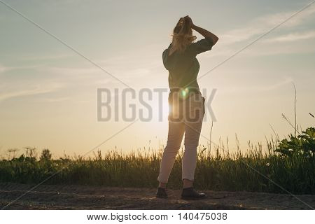 female teen girl stand in the fields copy space for your info, sunset light