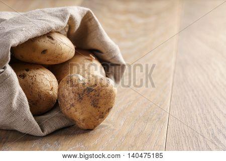 sack full of organic potatoes on oak wooden table, shallow focus