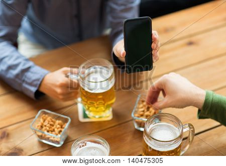 people, leisure, friendship and technology concept - close up of two male friends drinking beer with snacks and showing smartphone black blank screen at bar or pub