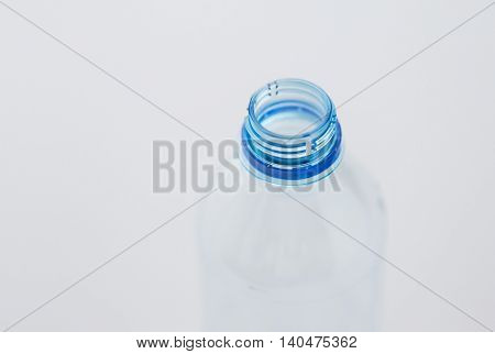 recycling, healthy eating and food storage concept - close up of clean empty used plastic water bottle neck