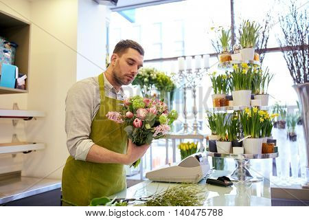 people, business, sale and floristry concept - florist man making bunch at flower shop