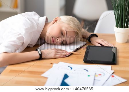 So tired. Calm woman having a rest with closed eyes on her workplace with a notebook and a tablet on it