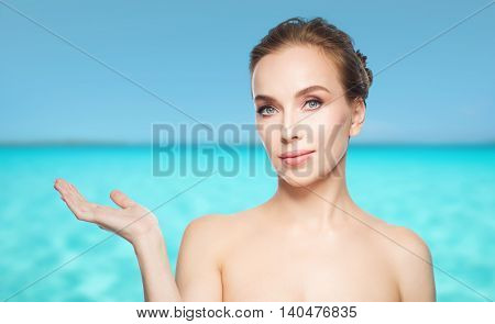 beauty, people, advertisement and health concept - smiling young woman holding something on palm of her hand over blue sea and sky background