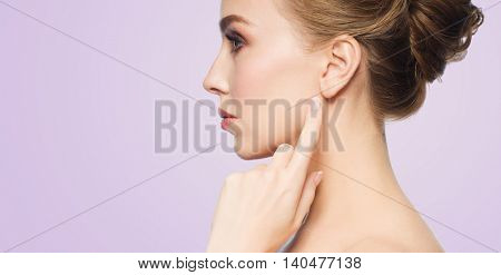 health, people and beauty concept - beautiful young woman pointing finger to her ear over violet background