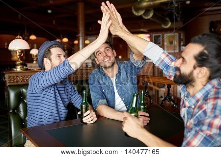 people, leisure, friendship, gesture and bachelor party concept - happy male friends drinking bottled beer and making high five at bar or pub