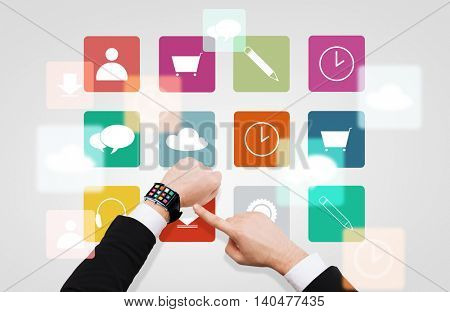 business, multimedia, people and modern technology concept - close up of businessman hand pointing to smart watch with menu icons on screen