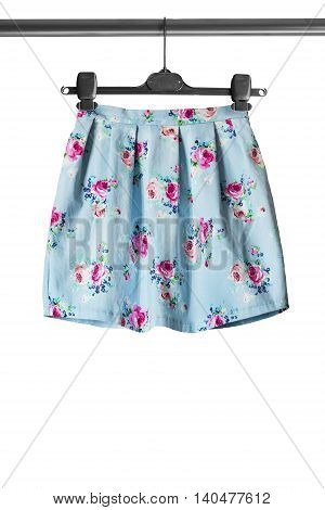 Blue floral pattern skirt on clothes rack isolated over white
