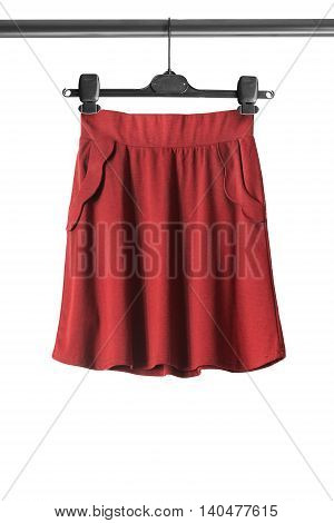 Red flared skirt on clothes rack isolated over white