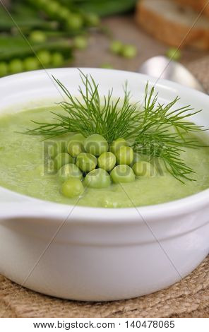 A plate of soup puree of green peas with dill on a table