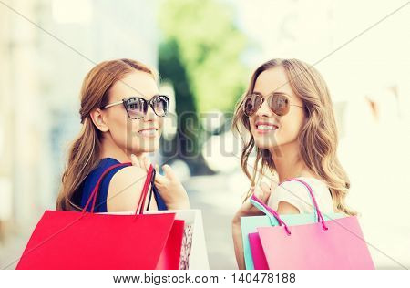sale, consumerism and people concept - happy young women in sunglasses with shopping bags on city street