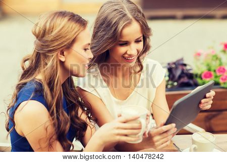 technology, lifestyle, friendship and people concept - happy young women or teenage girls with tablet pc computer drinking coffee at outdoor cafe