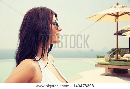 summer vacation, tourism, travel, holidays and people concept -face of smiling young woman in swimsuit with sunglasses over hotel resort infinity edge pool or beach background