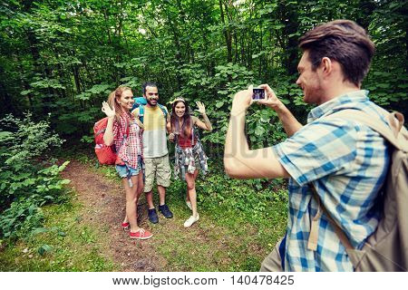 technology, travel, tourism, hike and people concept - group of smiling friends with backpacks taking picture by smartphone and waving hands in woods