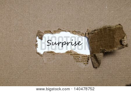 The word surprise appearing behind torn paper