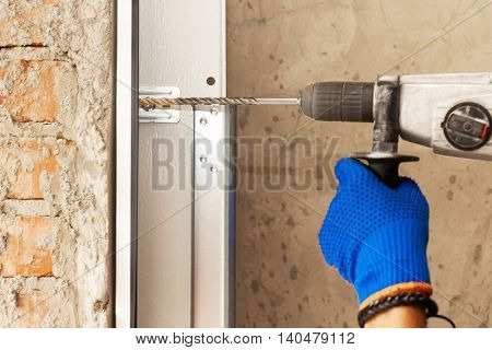 Garage doors installation. Worker drills a hole for the bolt