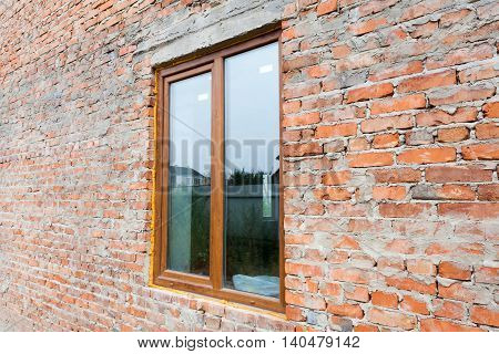 Single plastic window on a wall with red bricks. nstall window against brick wall facade.