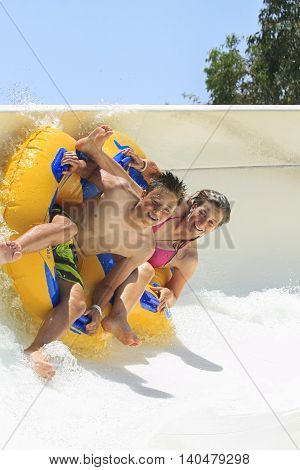 FfalirakiRhodes Greece-July.22016:Brother and siste drive with tube on the rafting slide in the Water park.Rafting slide is one of many popular game for adults and children in park.Water Water Park is located in Faliraki on the island of Rhodes in Greece