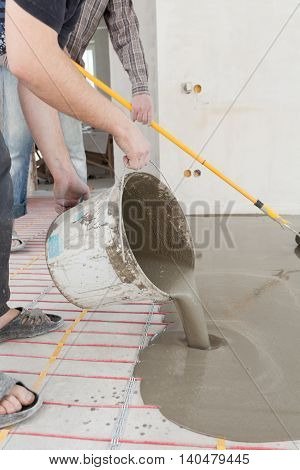 Electric floor heating system installation in new house. Worker pouring concrete on the floor