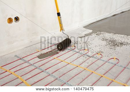 Electric floor heating system installation in new house. Closeup of concrete roller and red electrical wires