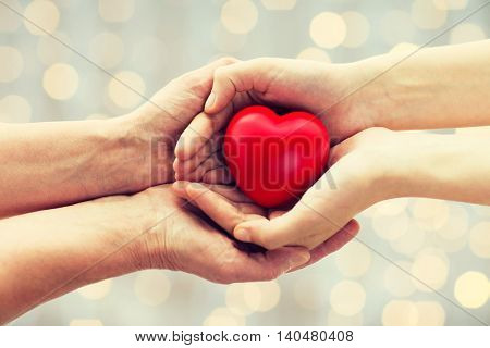 people, age, family, love and health care concept - close up of senior woman and young woman hands holding red heart over lights background