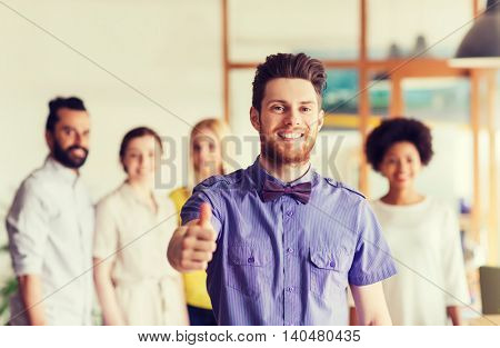 business, startup, people, gesture and teamwork concept - happy young man with beard and bow tie showing thumbs up over creative team in office